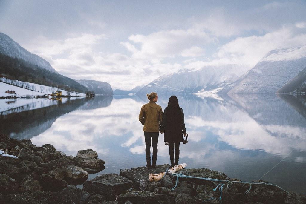 cặp đôi nắm tay ngắm hồ nước núi non