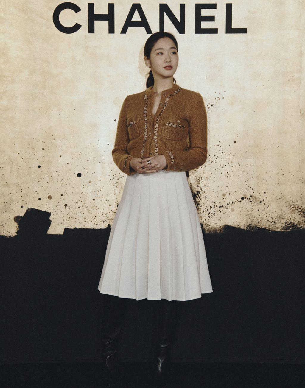 kim go eun mặc áo cardigan vải cashmere màu nâu và chân váy xếp li trắng tại chanel's métiers d'art show