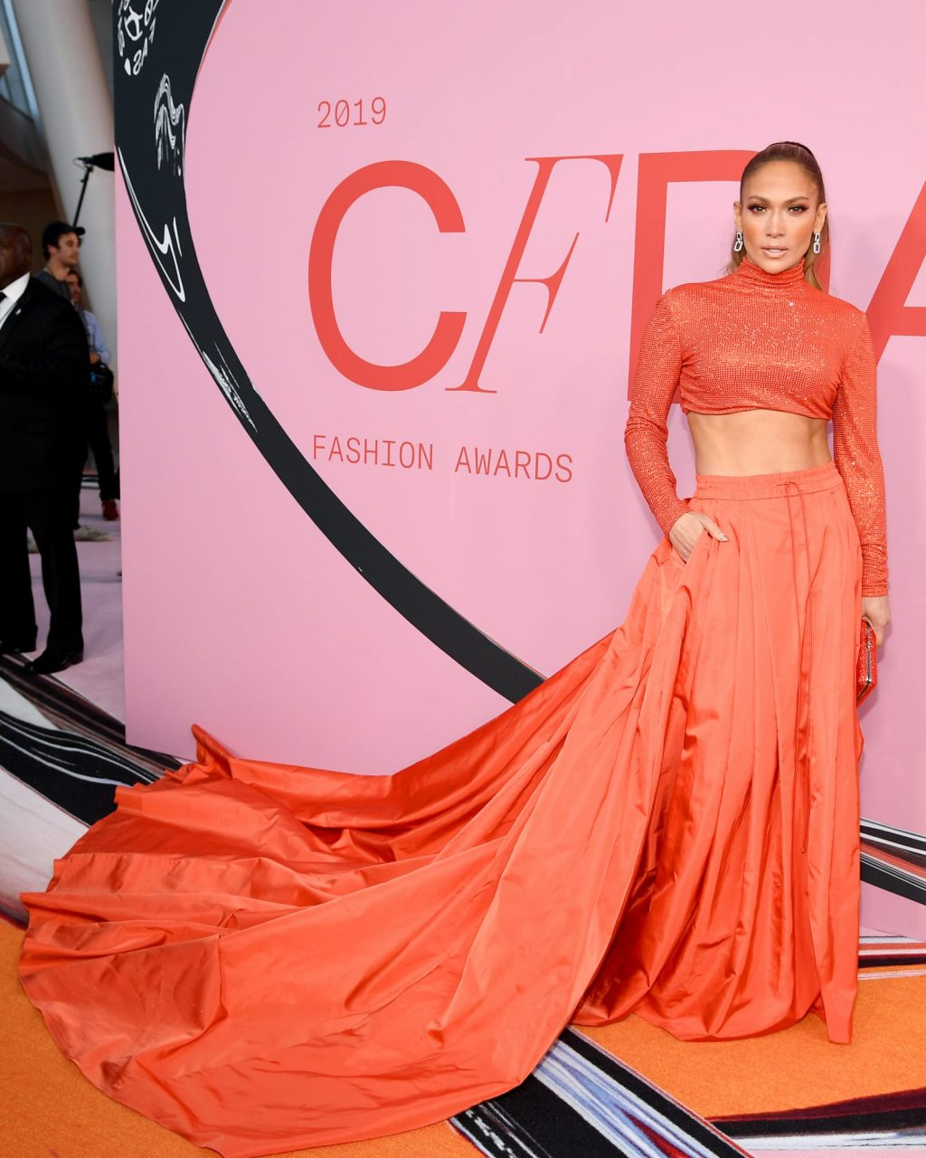 Jennifer Lopez mặc áo croptop chân váy ralph lauren màu cam sáng tại lễ trao giải cfda