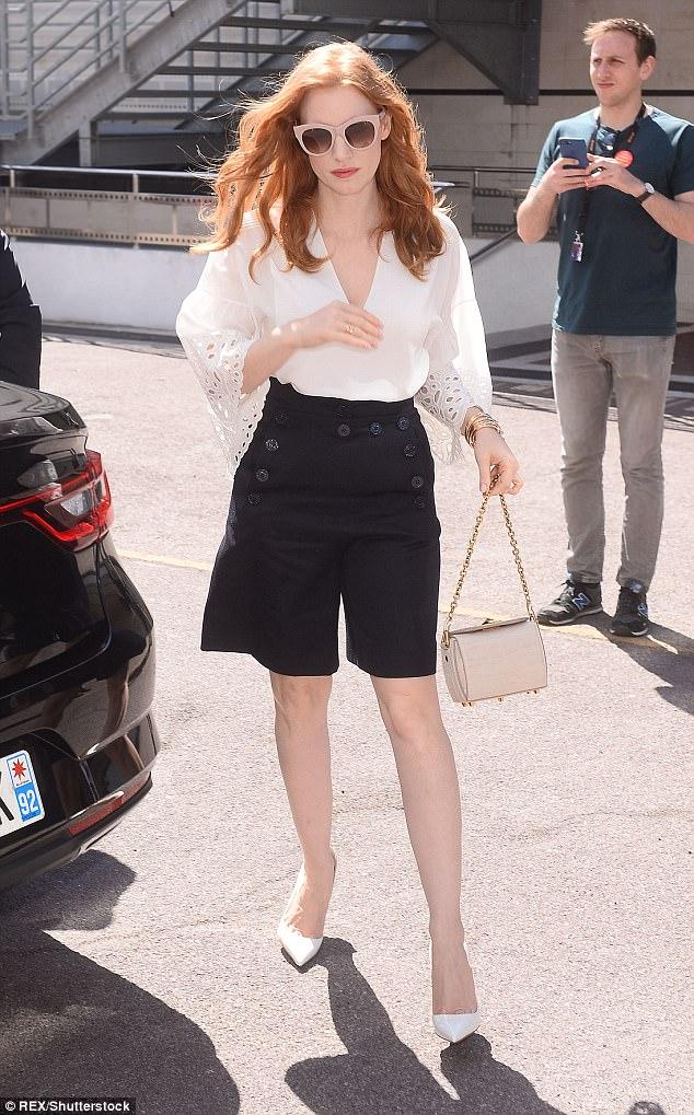 Jessica Chastain diện áo sơmi trắng cùng quần shorts đen thủy thủ và túi xách tại liên hoan phim cannes
