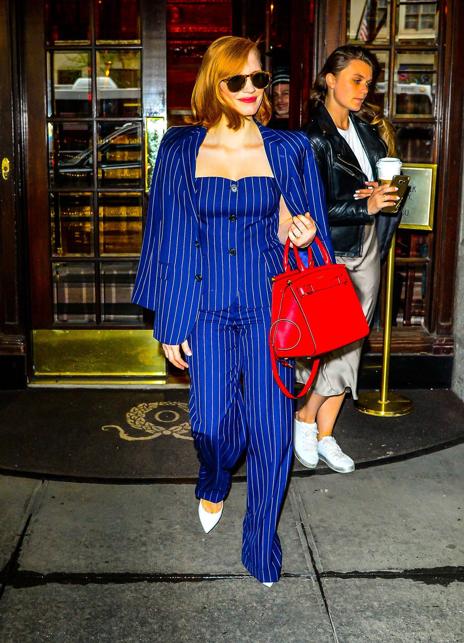 nữ diễn viên Jessica Chastain diện blazer kẻ sọc đồng bộ cùng quần âu và corset xanh cobalt của Ralp Lauren và kính mát đen, túi xách đỏ