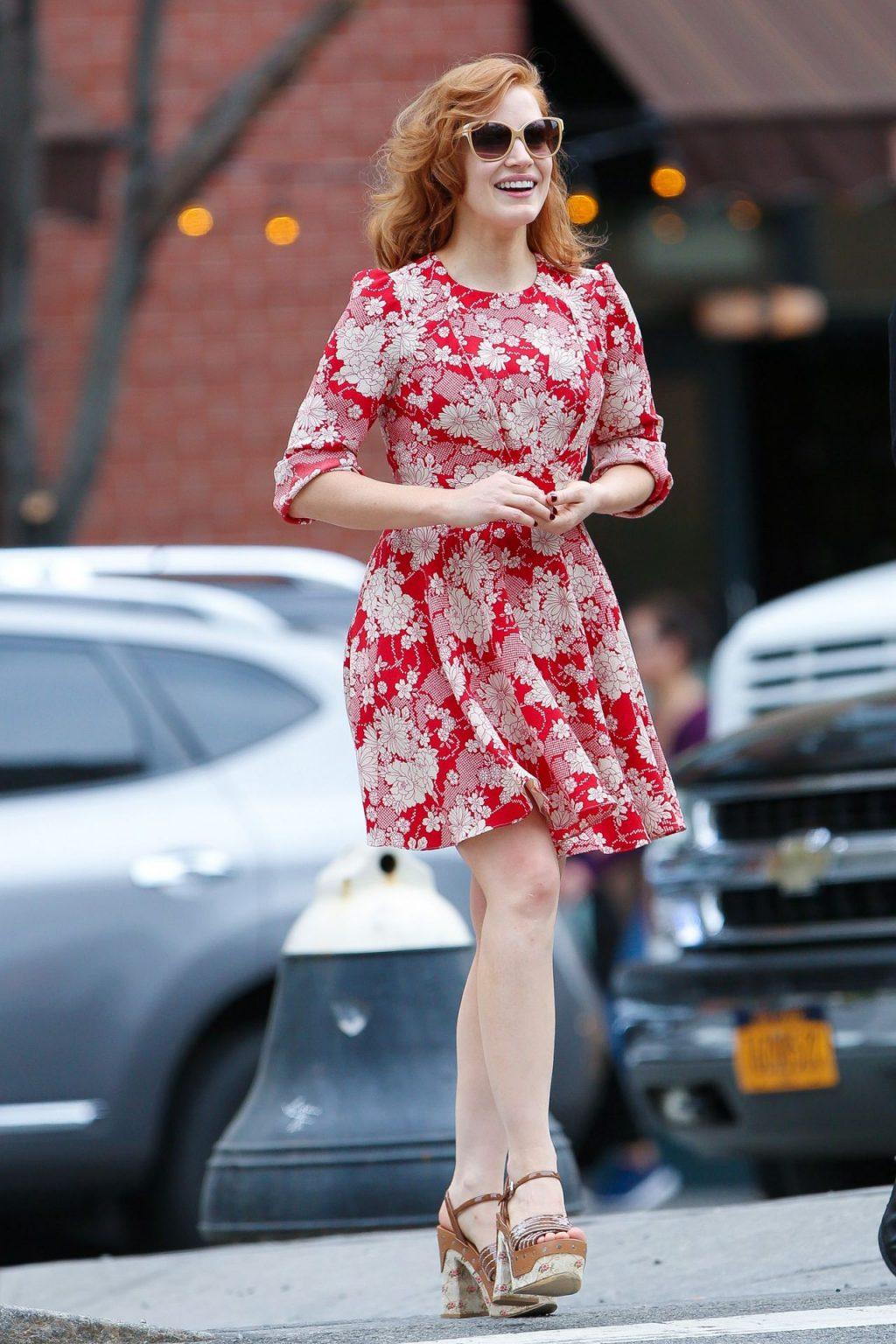 Jessica Chastain mặc đầm họa tiết hoa đỏ, kính mát gọng lớn, giày cao gót màu nâu trên đường phố cannes