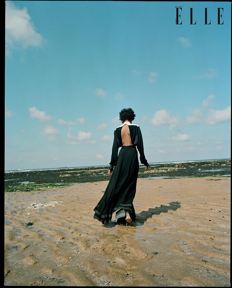 cô gái mặc đầm hở lưng Givenchy đi trên cát