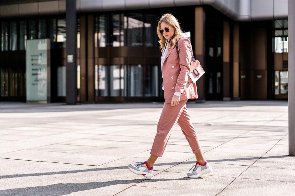 cô gái mặc suit hồng và giày thể thao