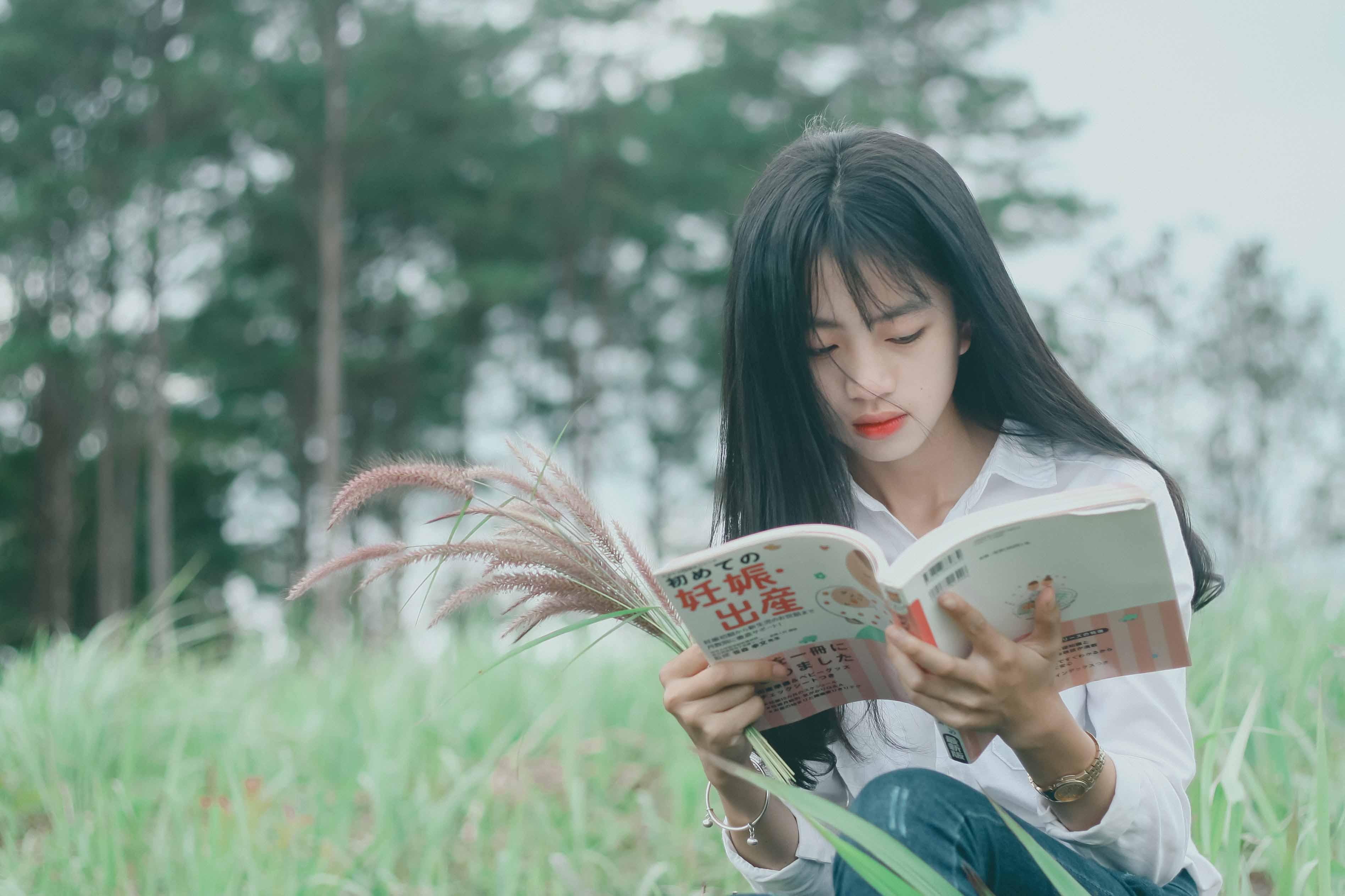 cô gái ngồi đọc sách trên đồng