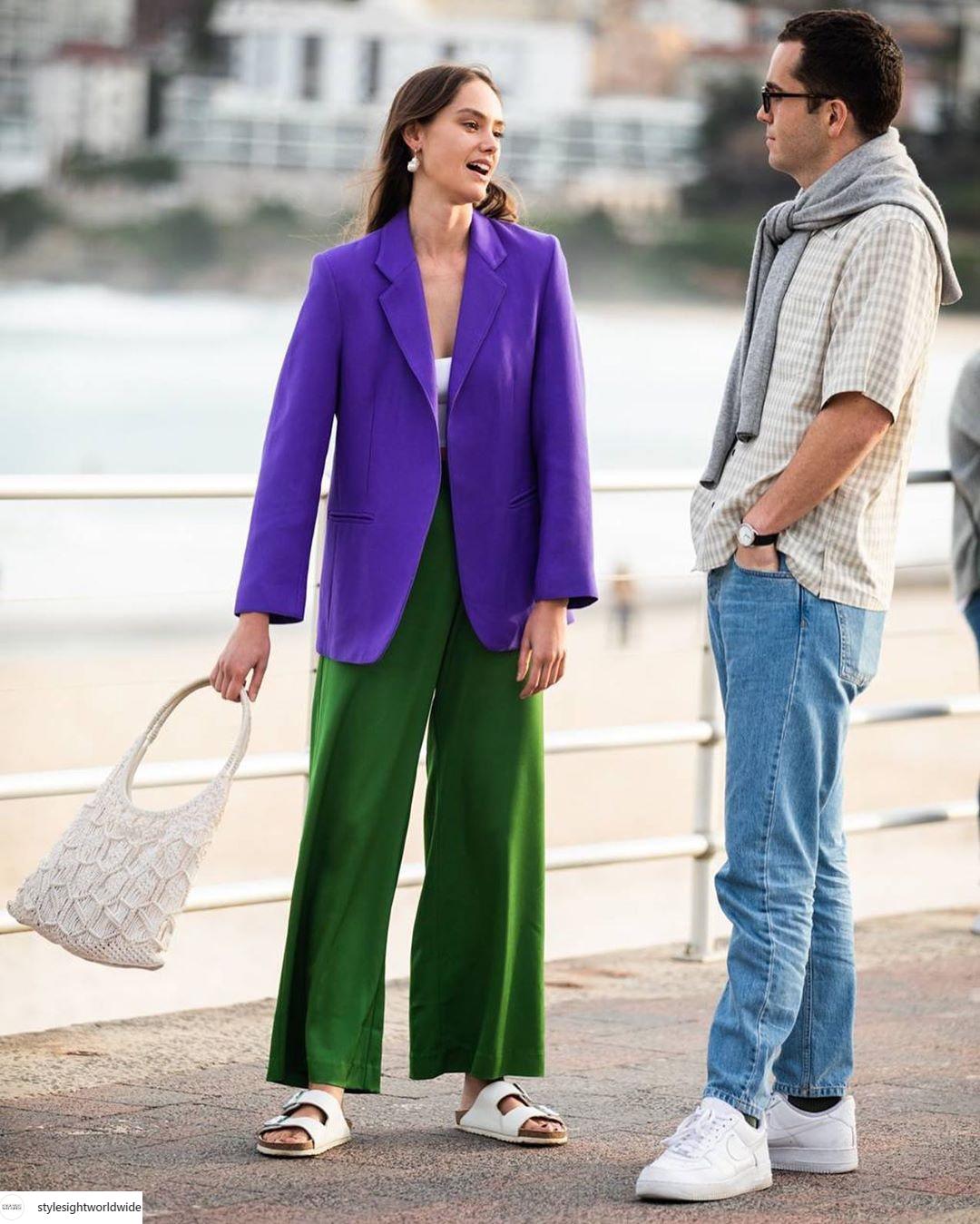quần ống loa màu xanh lá và áo khoác màu tím