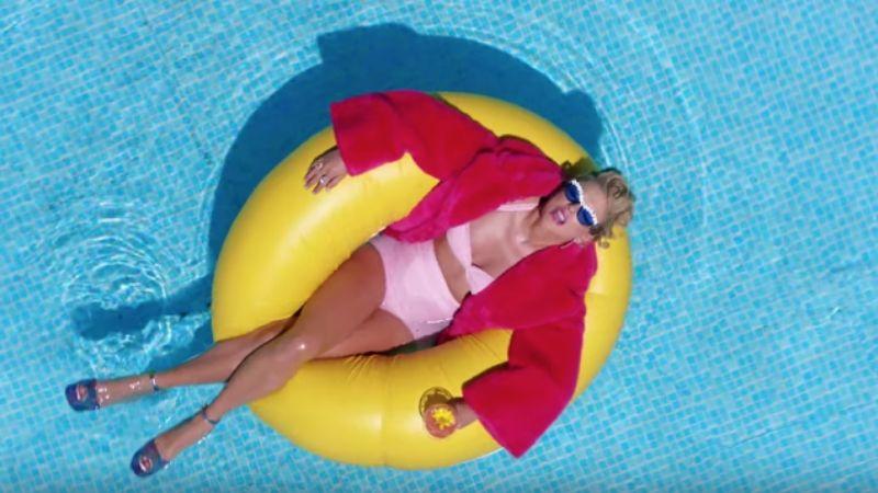 taylor swift mặc bikini và áo choàng màu hồng nằm trên hồ bơi