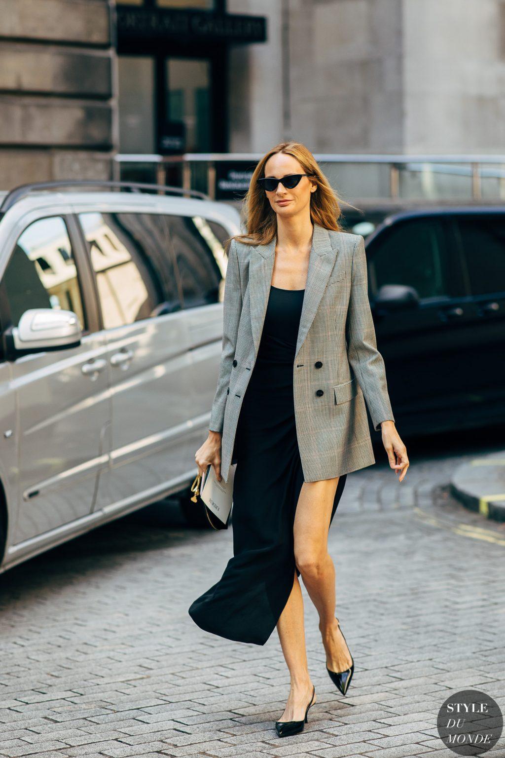 fashionista diện đầm đen, blazer xám, kính mát đen tuần lễ thời trang