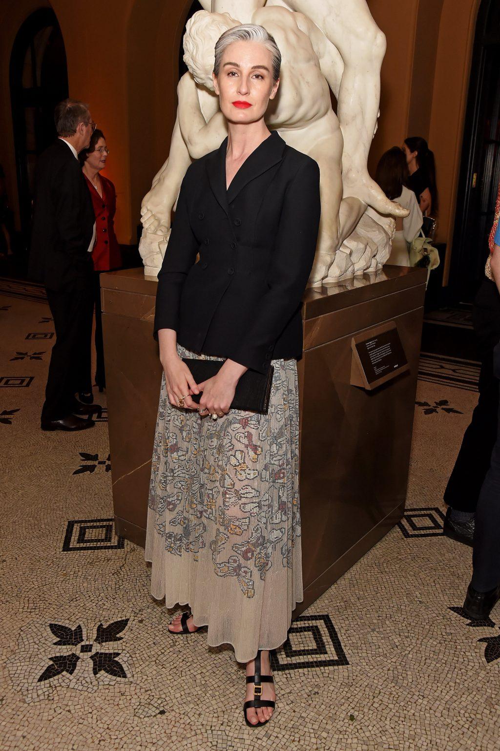 erin o'connor diện chân váy tulle màu kem kết hợp áo khóac lụa đen tại bữa tiệc mùa hè của dior