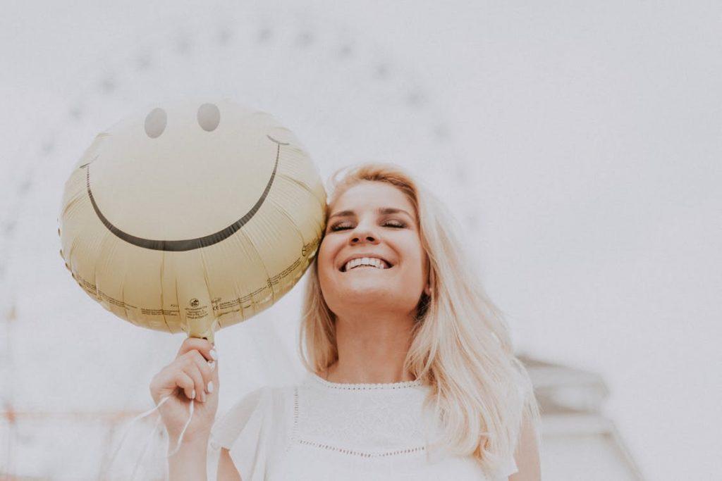 cô gái mỉm cười cầm bong bóng mặt cười