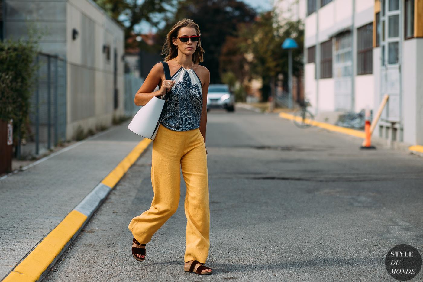 fashionista mặc áo yếm họa tiết, quần vàng, túi xách trắng, kính mát