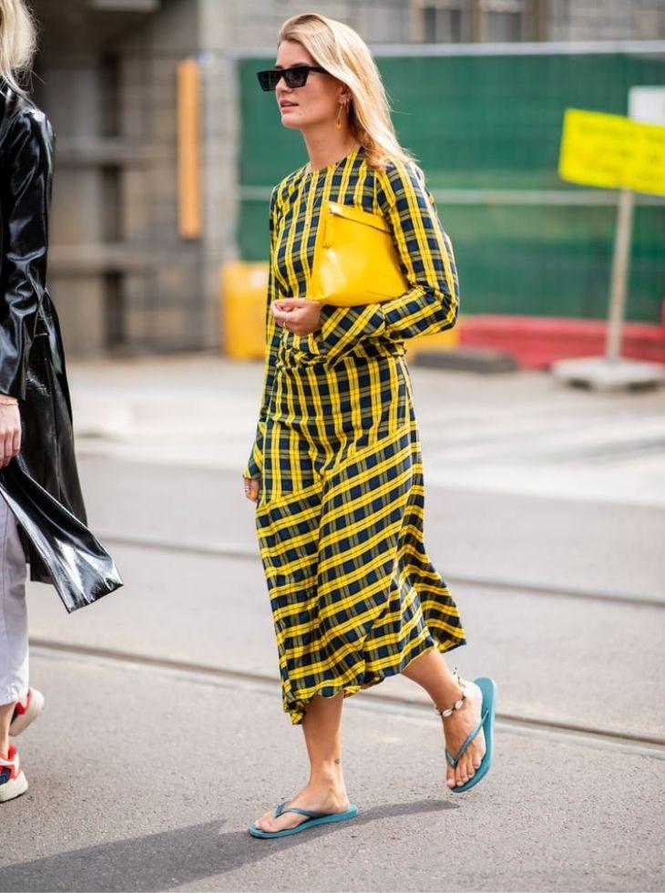 cô gái mặc đầm kẻ ô màu vàng và đi dép xỏ ngón