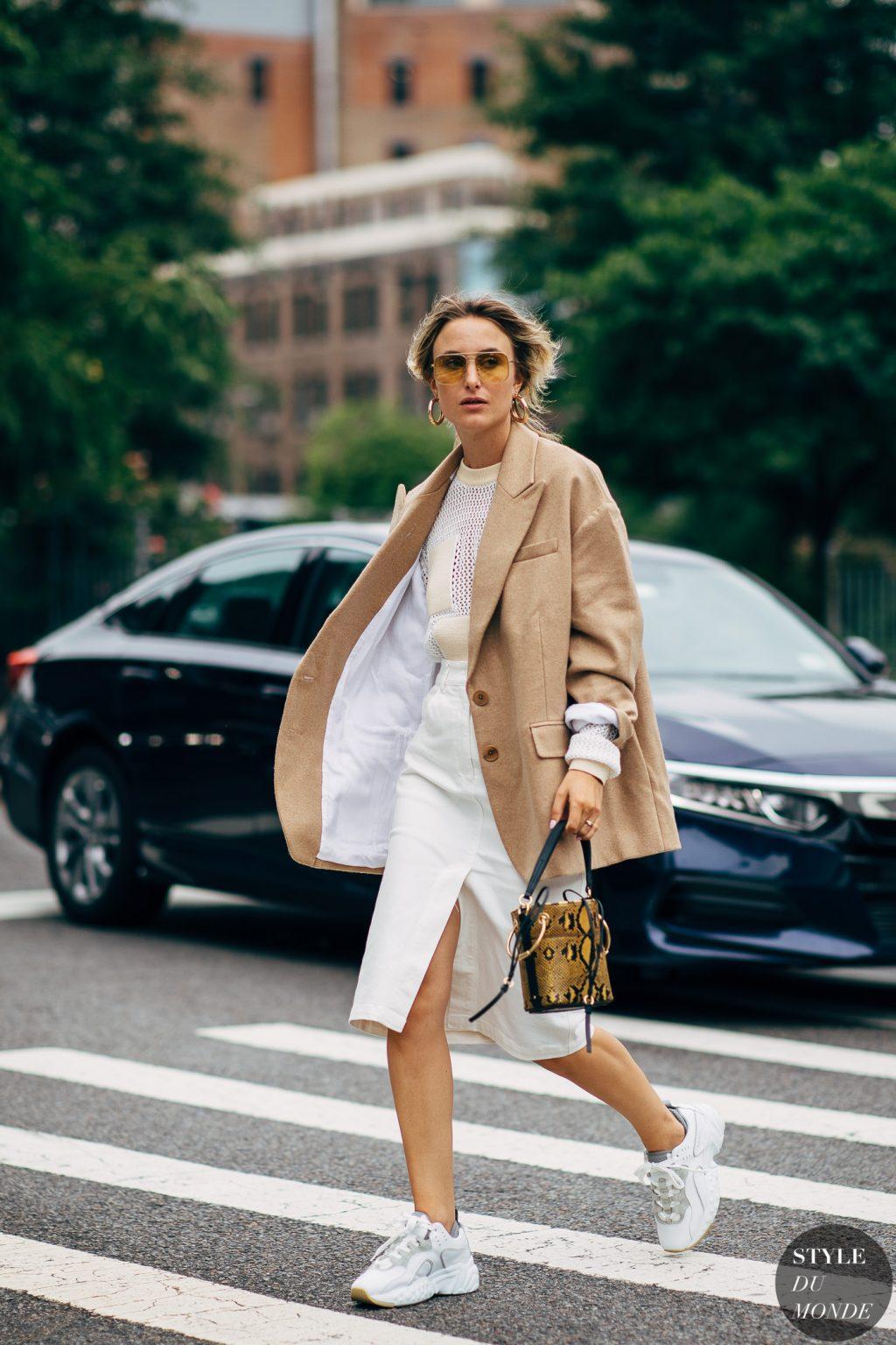 Rebecca Laurey diện blazer màu beige chân váy trắng kính mát tuần lễ thời trang new york
