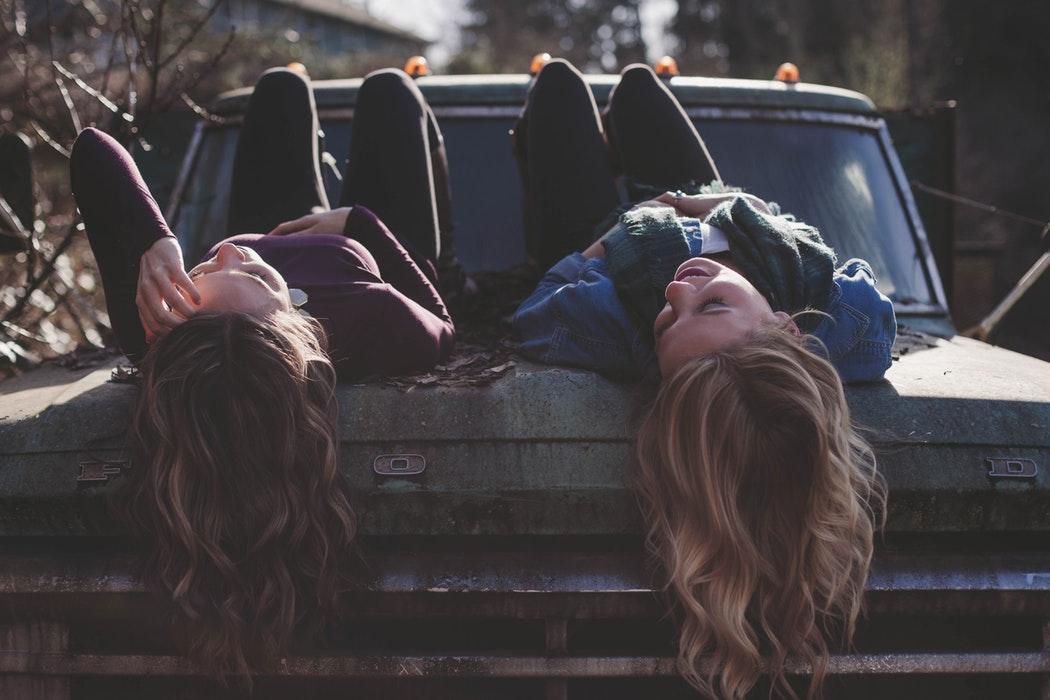 hai cô gái tóc dài nằm trên mui xe