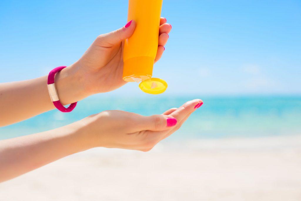 phụ nữ thoa kem chống nắng lên bàn tay