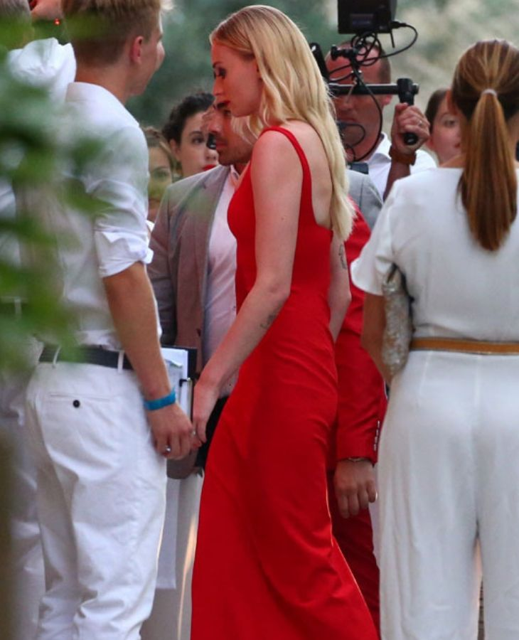 sophie turner mặc đầm suông dài màu đỏ tại bữa tiệc diễn tập
