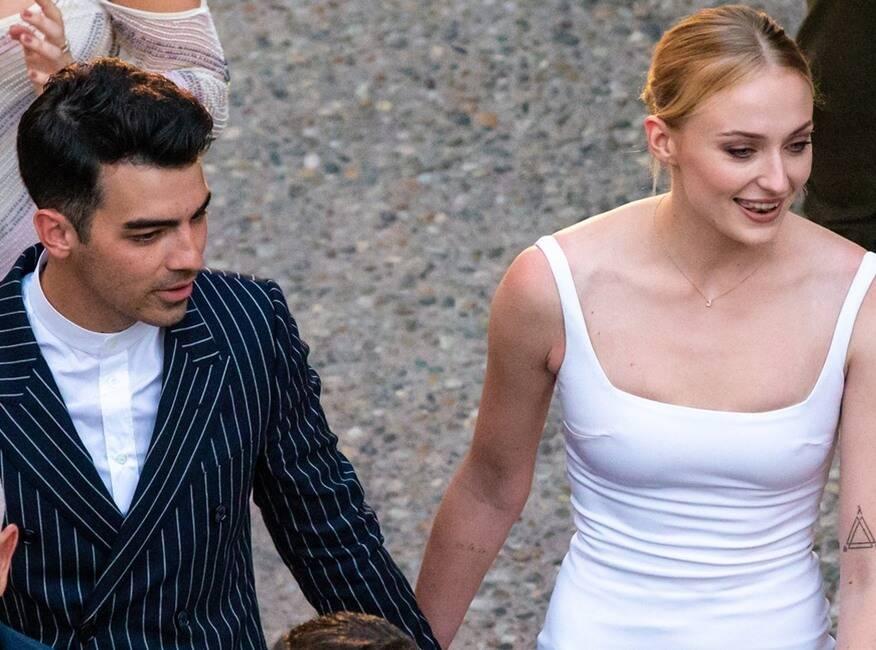 sophie turner mặc đầm trắng cổ vuông và joe jonas mặc vest đen sọc trắng tại buổi tiệc pre-wedding