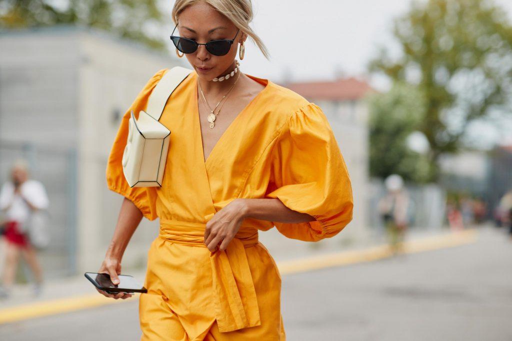 Fashionista mặc chiếc váy vàng cùng túi xách trắng và kính mắt đen
