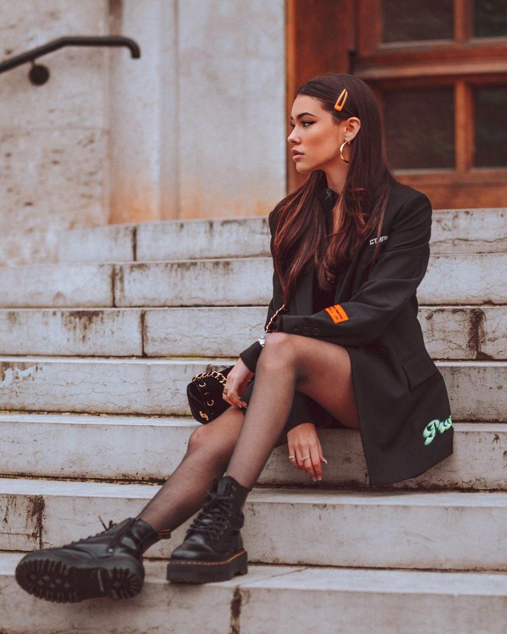 Madison mặc áo vest và đi giày đen