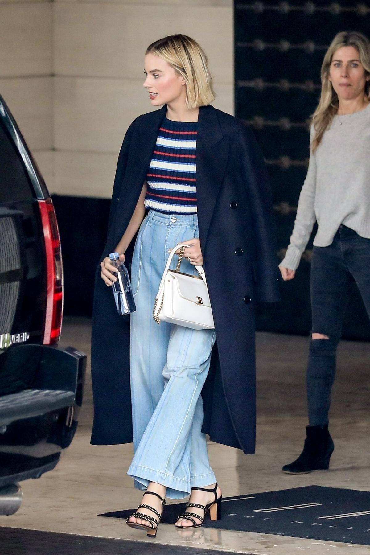 margot robbie mặc áo trench coat xanh navy áo kẻ sọc ngang quần jeans