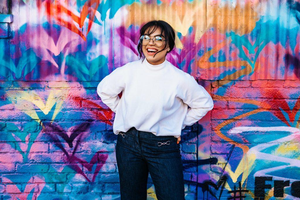 cô gái cười đứng trước bức tường sắc màu