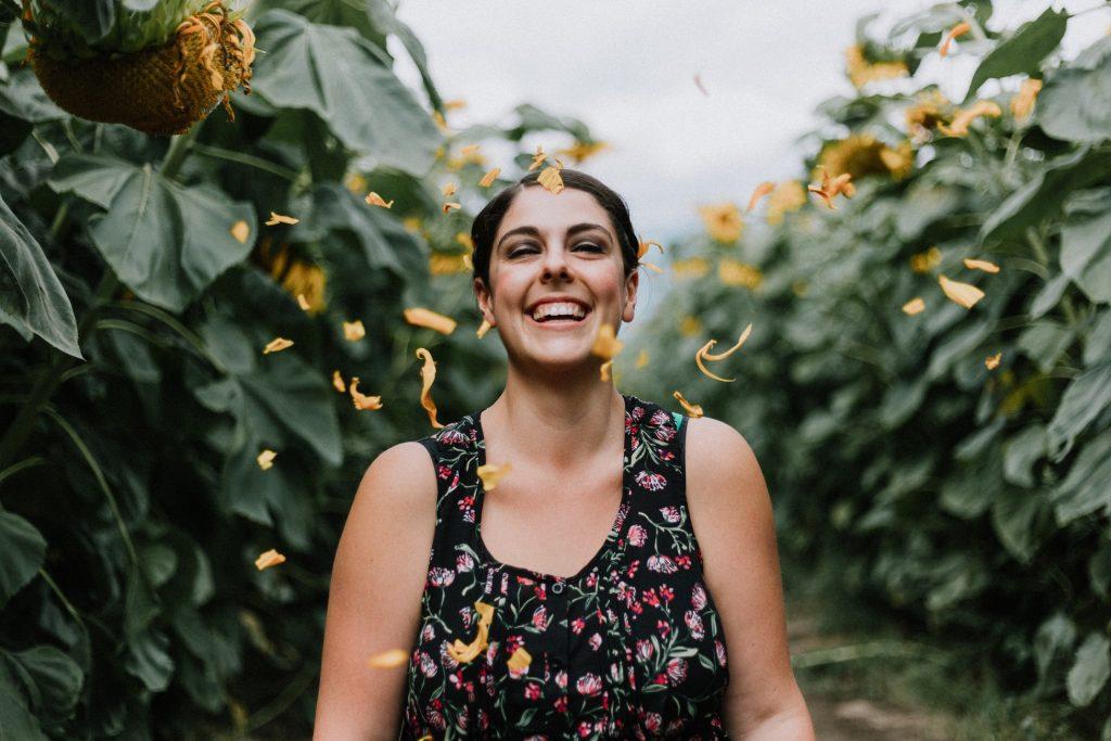 cô gái cười giữa những cánh hoa