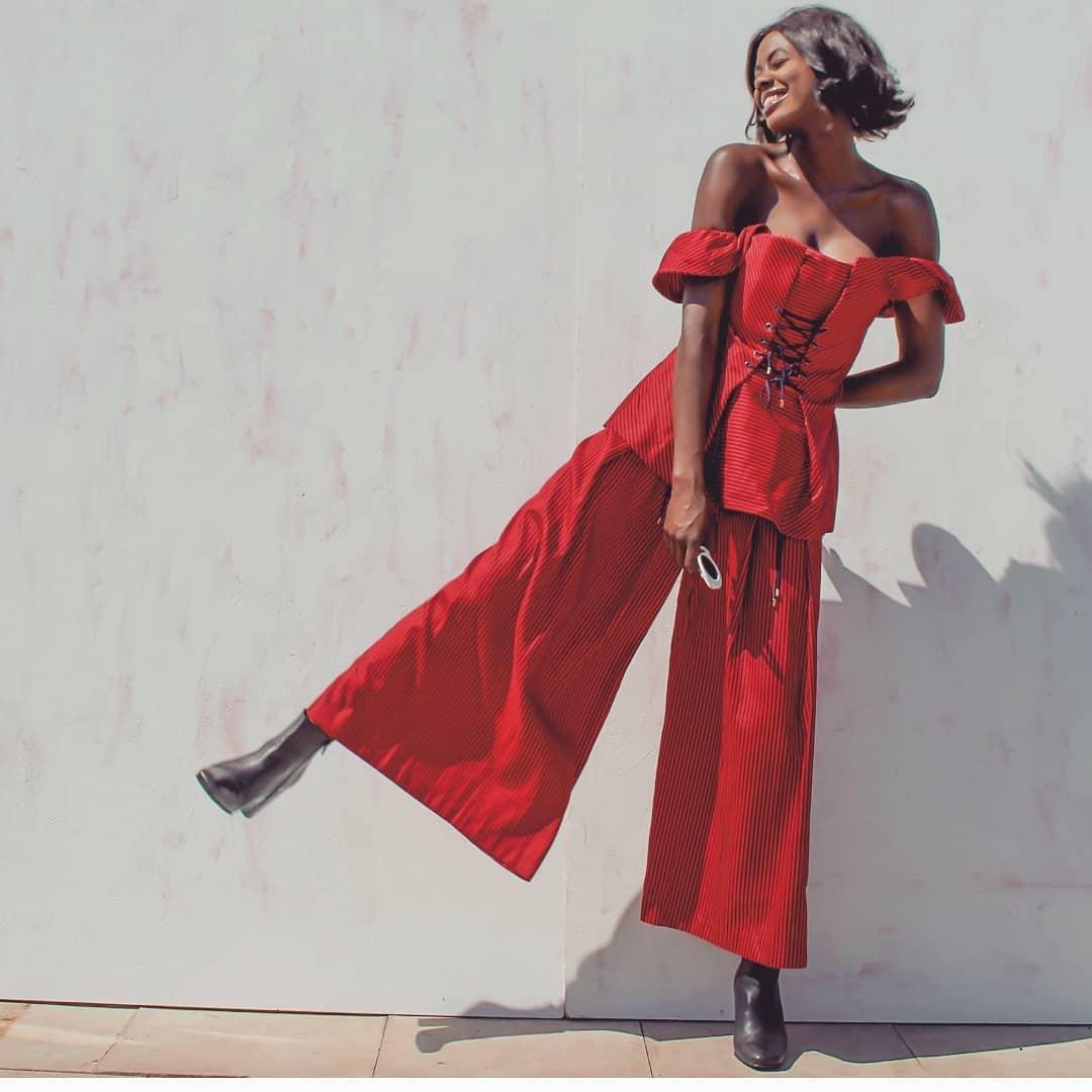 Fashionista mặc áo trễ vai và quần ống rộng màu đỏ cùng đôi giày đen