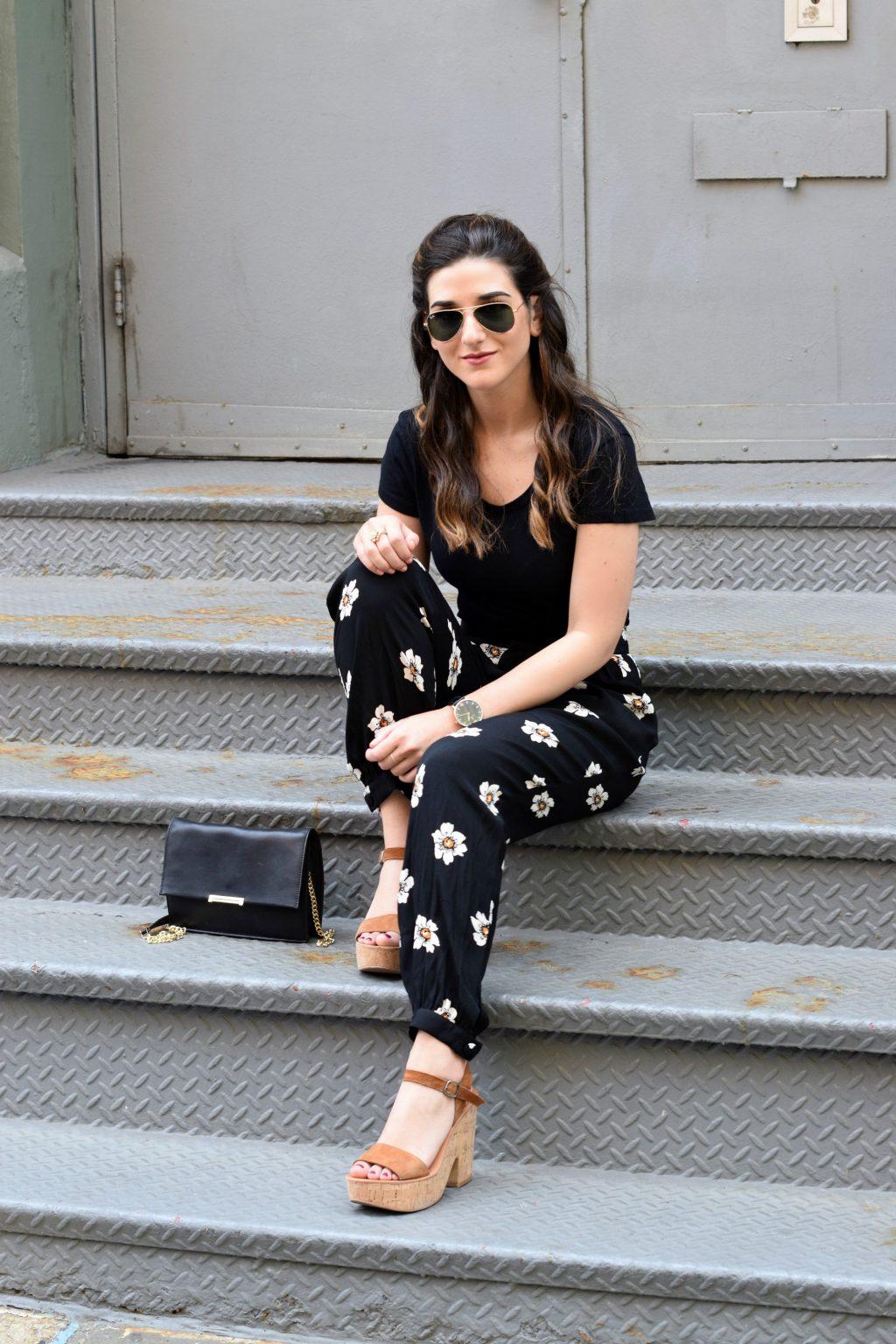 Người mẫu mặc áo đen cùng quần dài hoạ tiết hoa