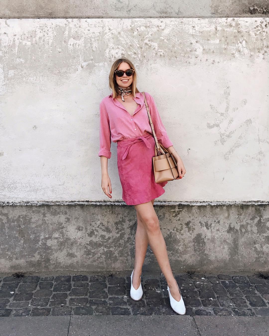 Người mẫu mặc áo sơ mi màu hồng nhạt, chân váy hồng đậm và đi giày trắng