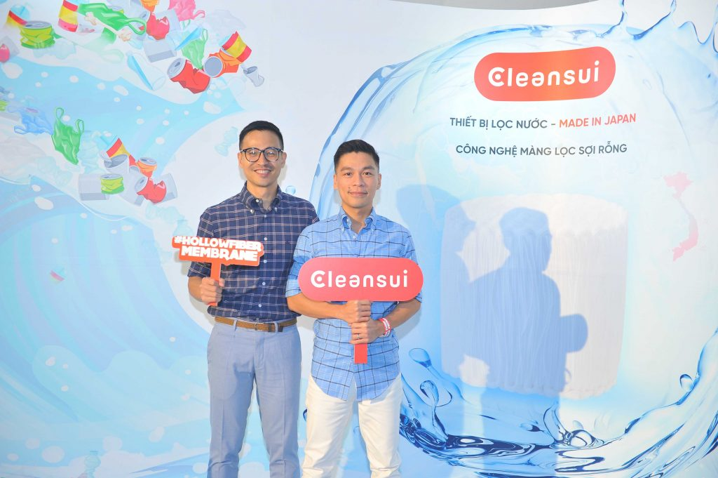 Cặp đôi Adrian Anh Tuấn và Sơn Đoàn tại quầy trải nghiệm sản phẩm lọc nước Mitsusbishi Cleansui cho phòng giặt.