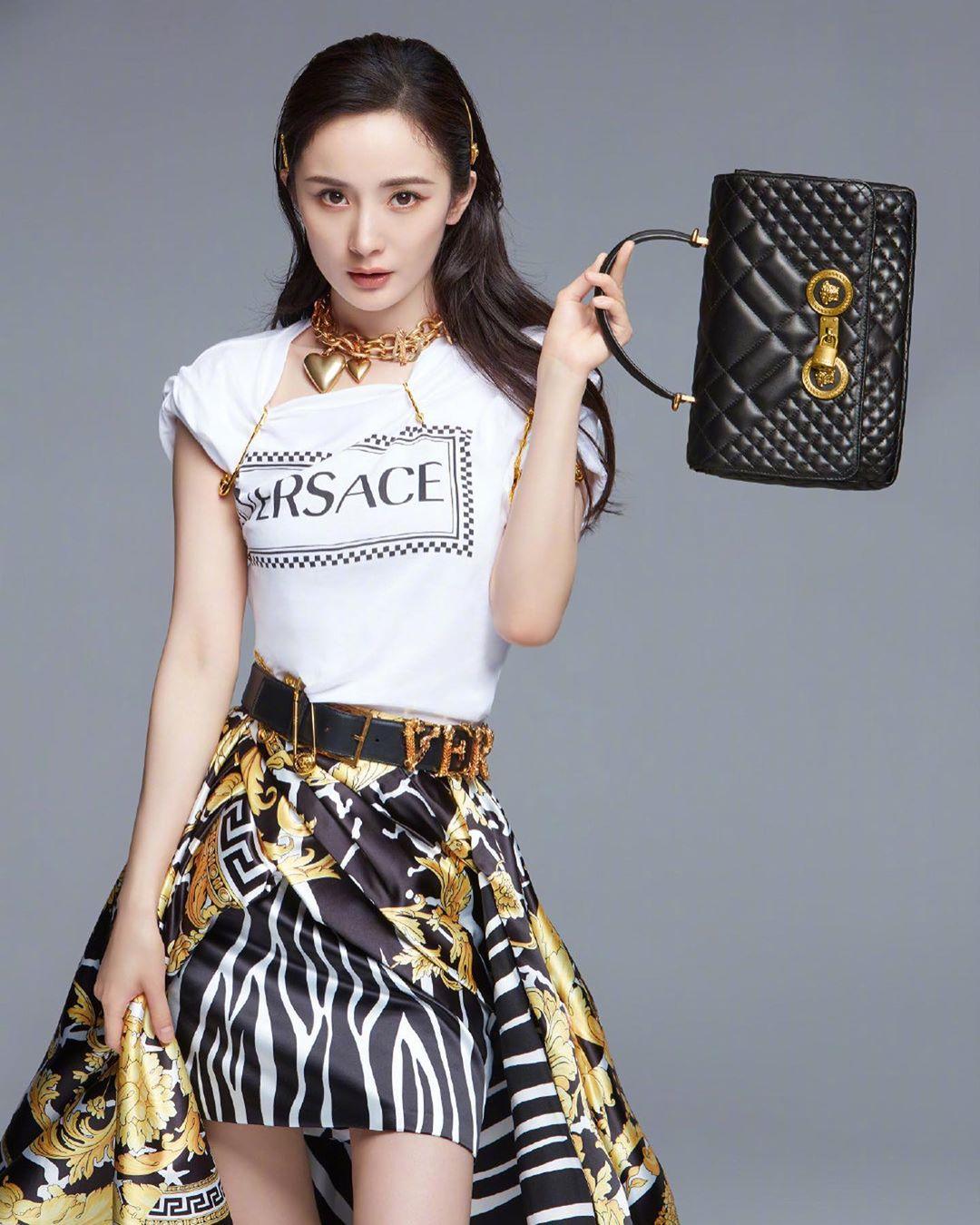 Dương Mịch mặc áo trắng kết hợp cùng chân váy và mang túi xách đen của Versace