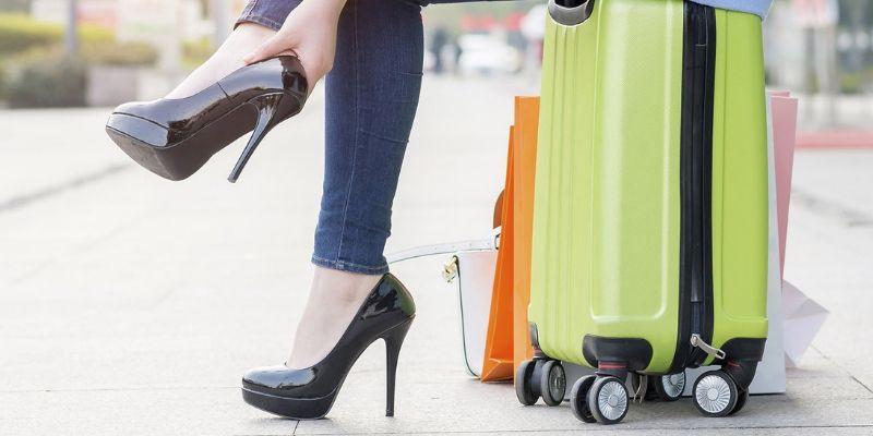 Giày cao gót đen đế kép cùng vali màu xanh