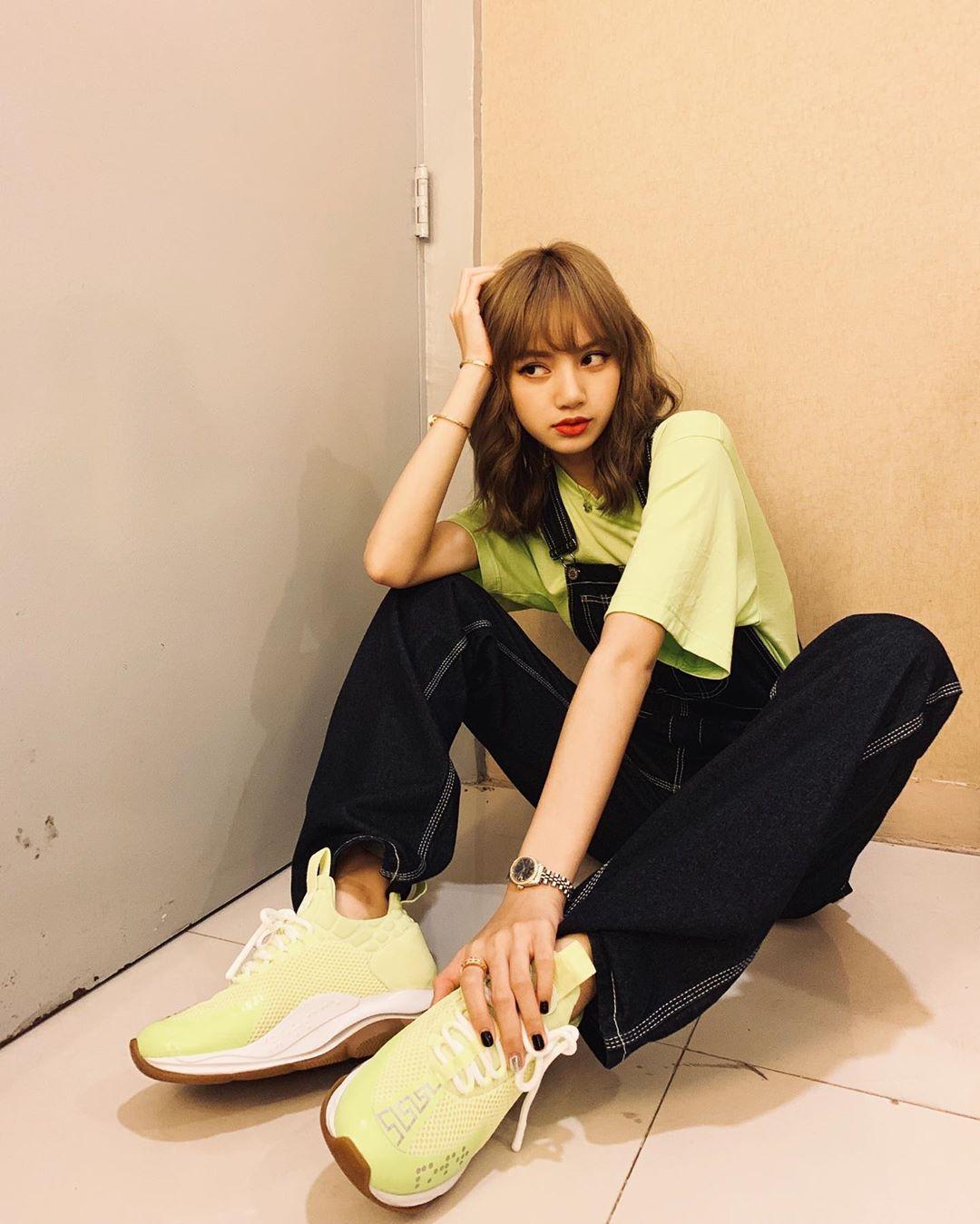 Lisa mặc áo và đi giày xanh, phối cùng quần đen