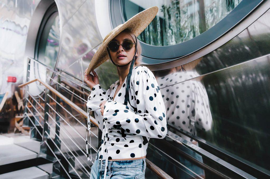 Người mẫu mặc áo trắng chấm bi đen và đội mũ coi bản to