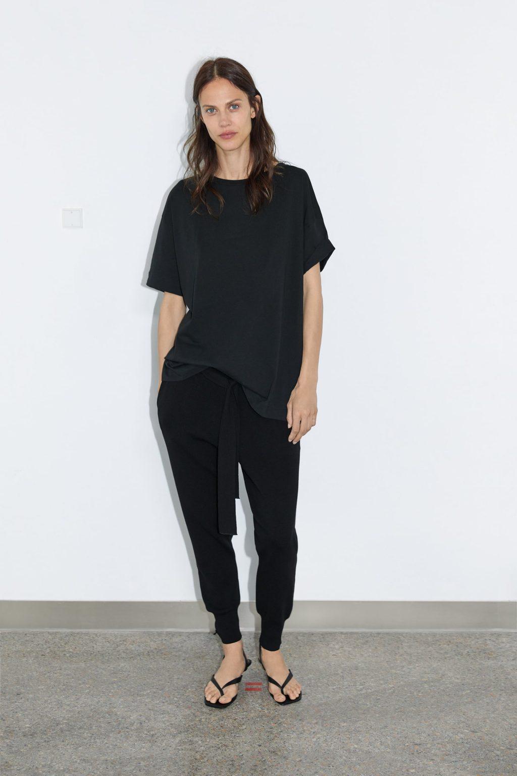 Người mẫu mặc áo phông đen cùng quần jogger đen