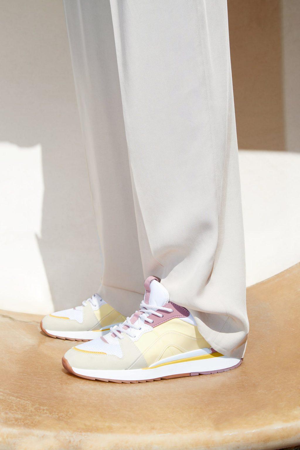Người mẫu mặc quần dài trắng và đi giày sneaker