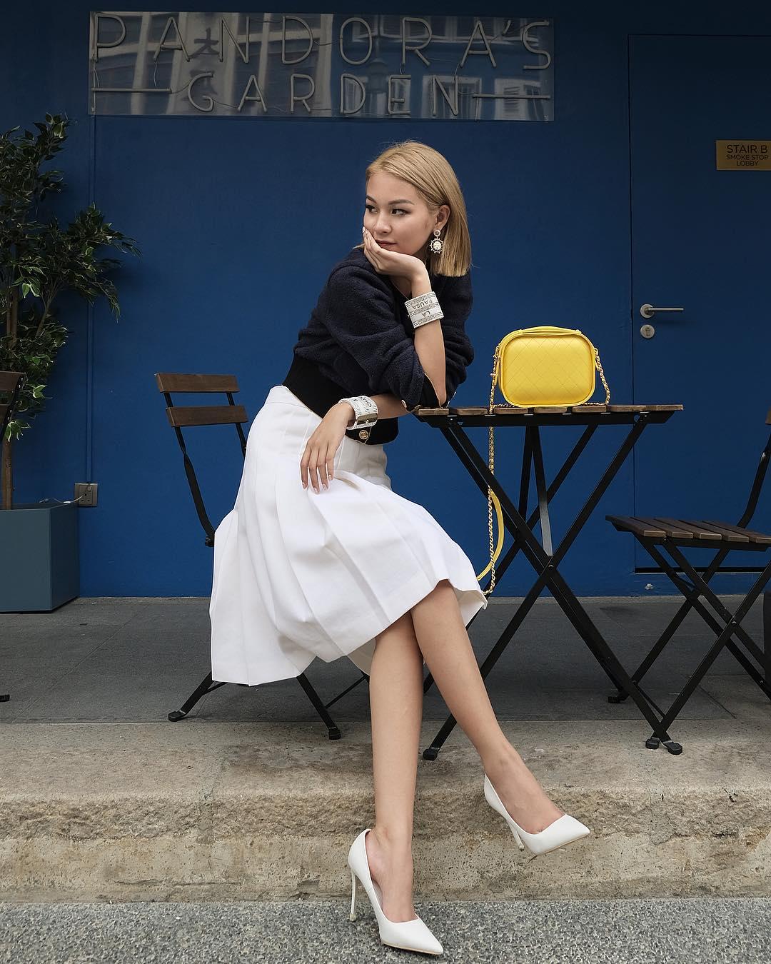Phí Phương Anh mặc chân váy midi trắng và áo tay dài đen cho thời trang du lịch Đà Lạt