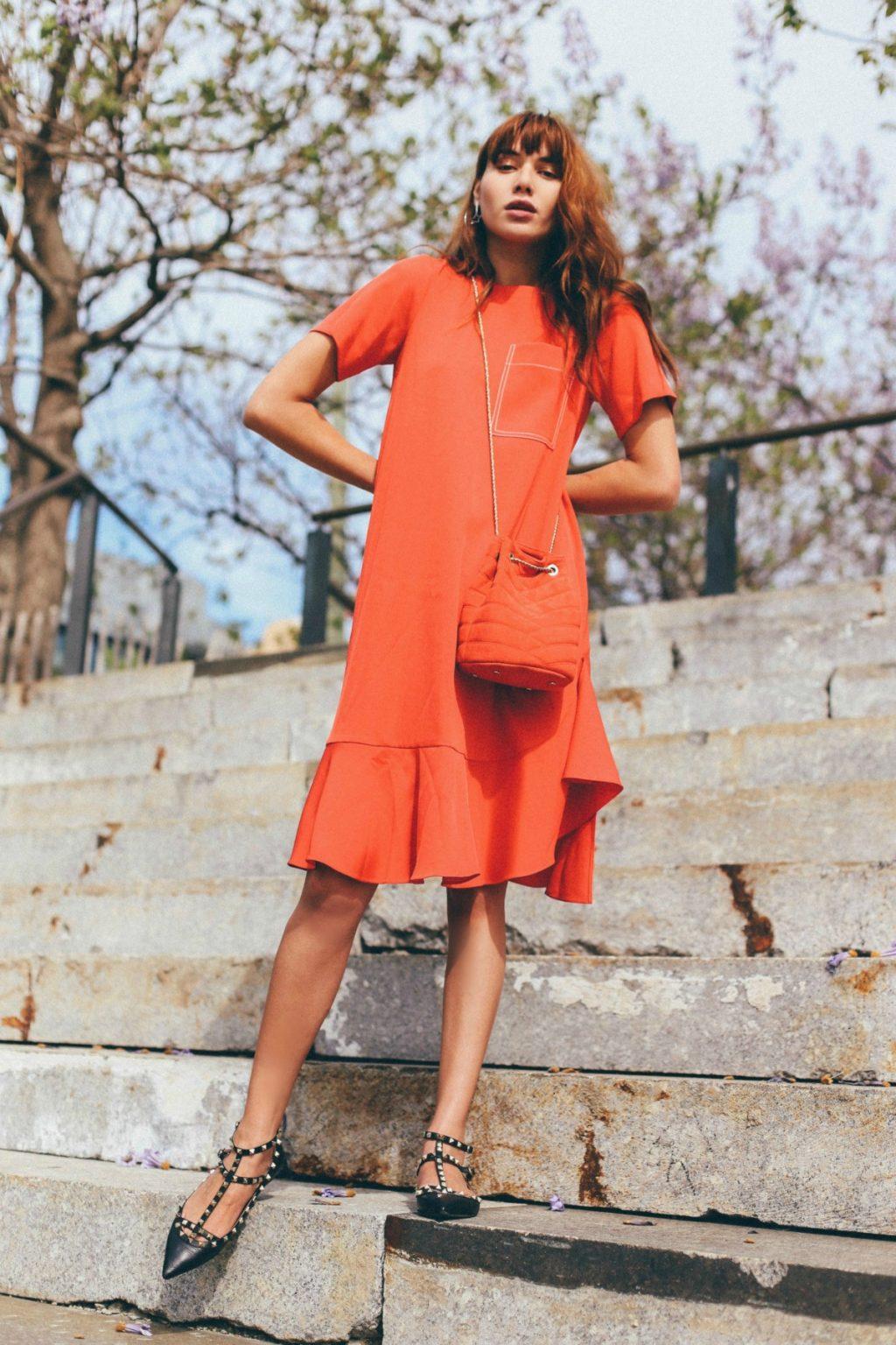 Fahionista mặc váy màu cam và đi giày bệt đen
