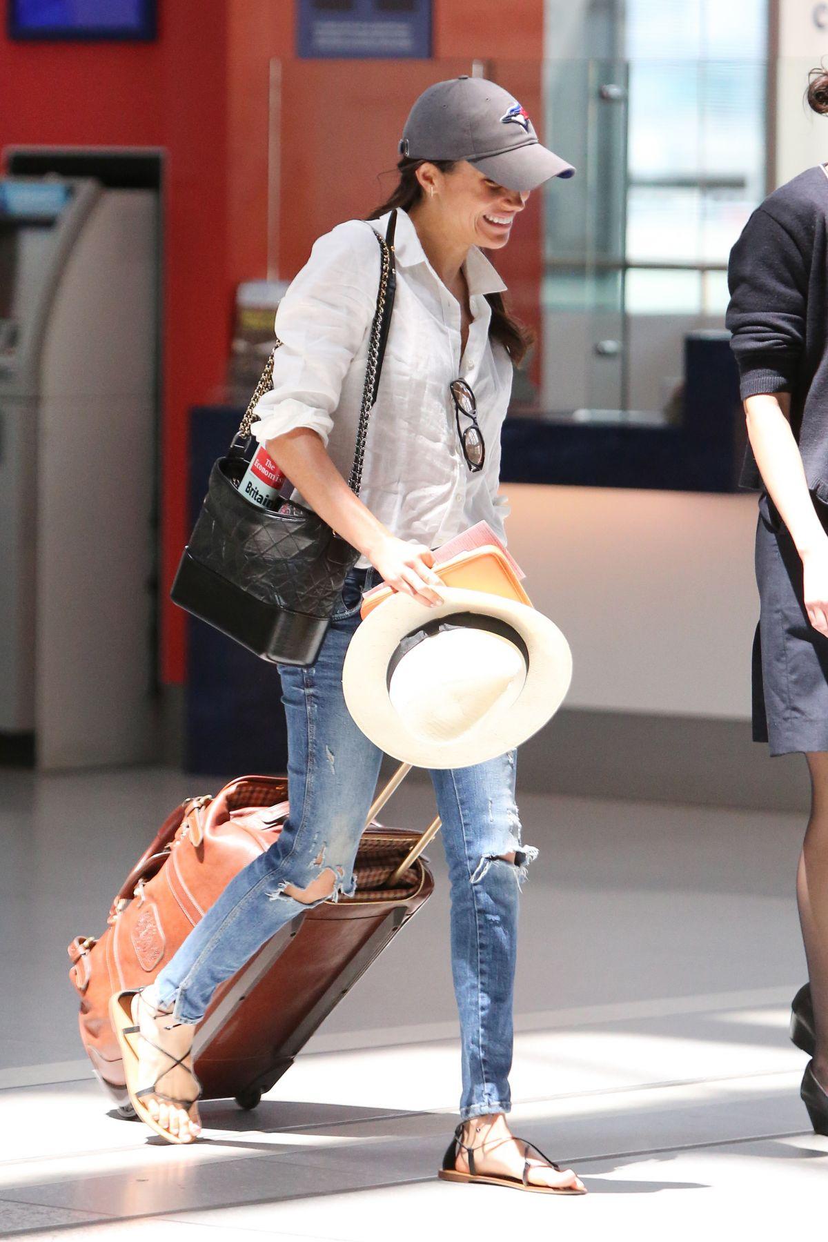 Meghan Markle mặc áo trắng quần jeans và đeo túi xách đen