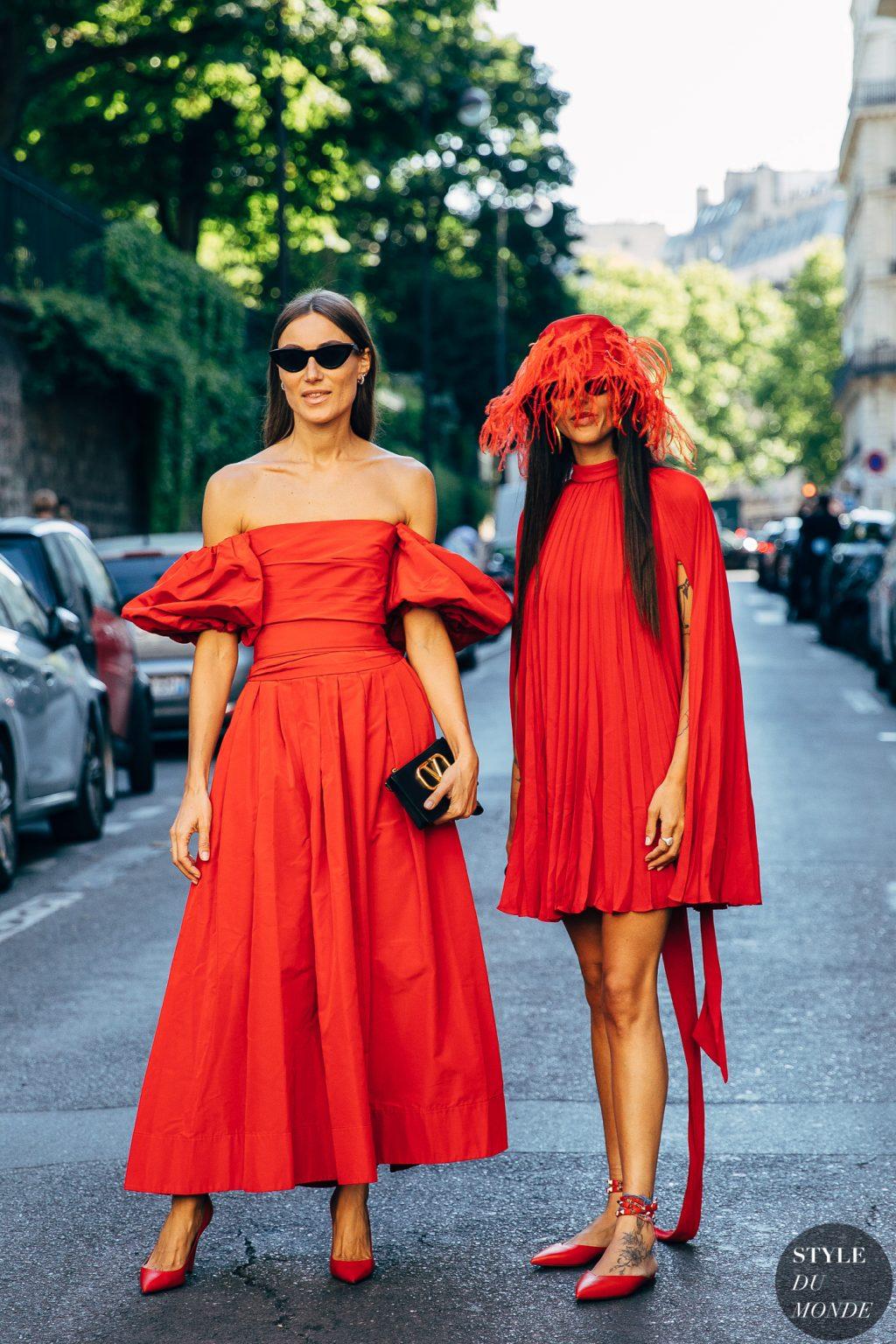 Người mẫu mặc váy cam đỏ cầm clutch đen
