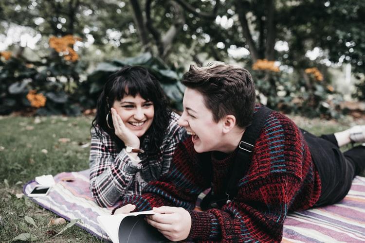 hai cô gái nằm trên cỏ tươi cười
