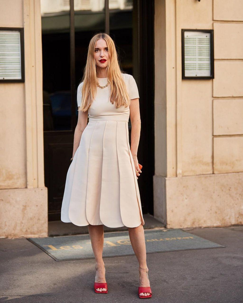 Fashionista mặc váy trắng đi giày mũi vuông màu đỏ