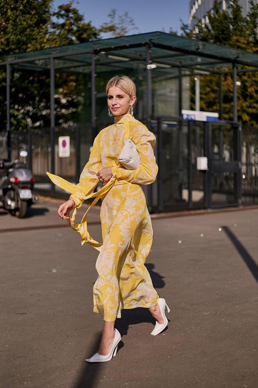 Fashionista mặc váy vàng đi giày mũi vuông màu trắng