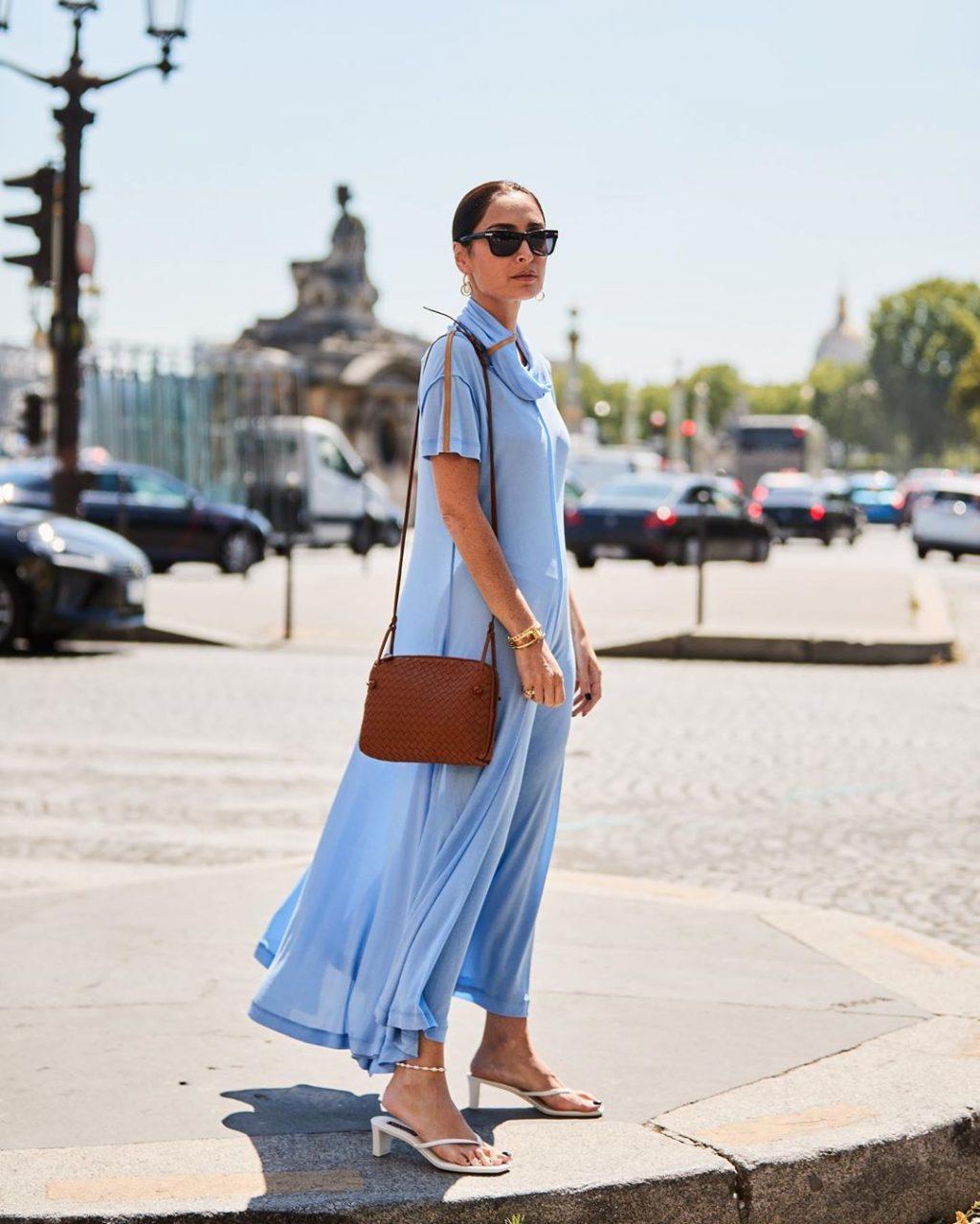 Fashionista mặc váy xanh thiên thanh, đeo kính mắt đen và đi giày mũi vuông trắng