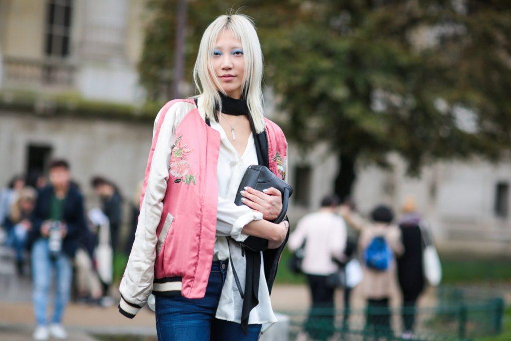 sora choi tóc vàng mặc áo khoác bomber màu hồng và sơ mi trắng
