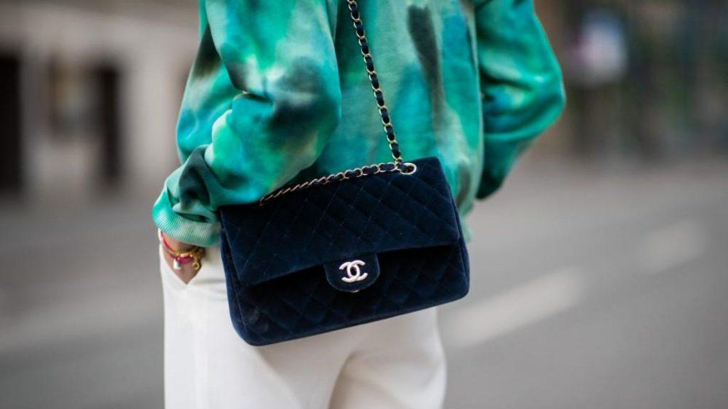 người mẫu mặc áo màu xanh và túi da lộn Chanel