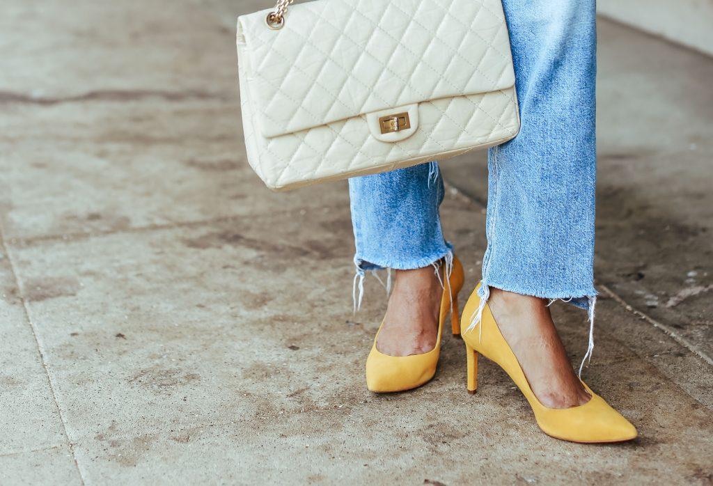 Người mẫu mặc quần denim mang túi trắng và giày da màu vàng