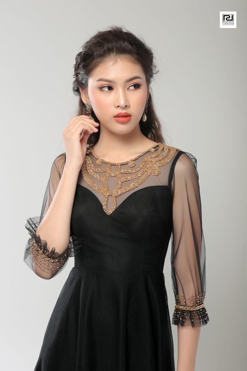 Người mẫu mặc váy đen hoạ tiết ren màu vàng