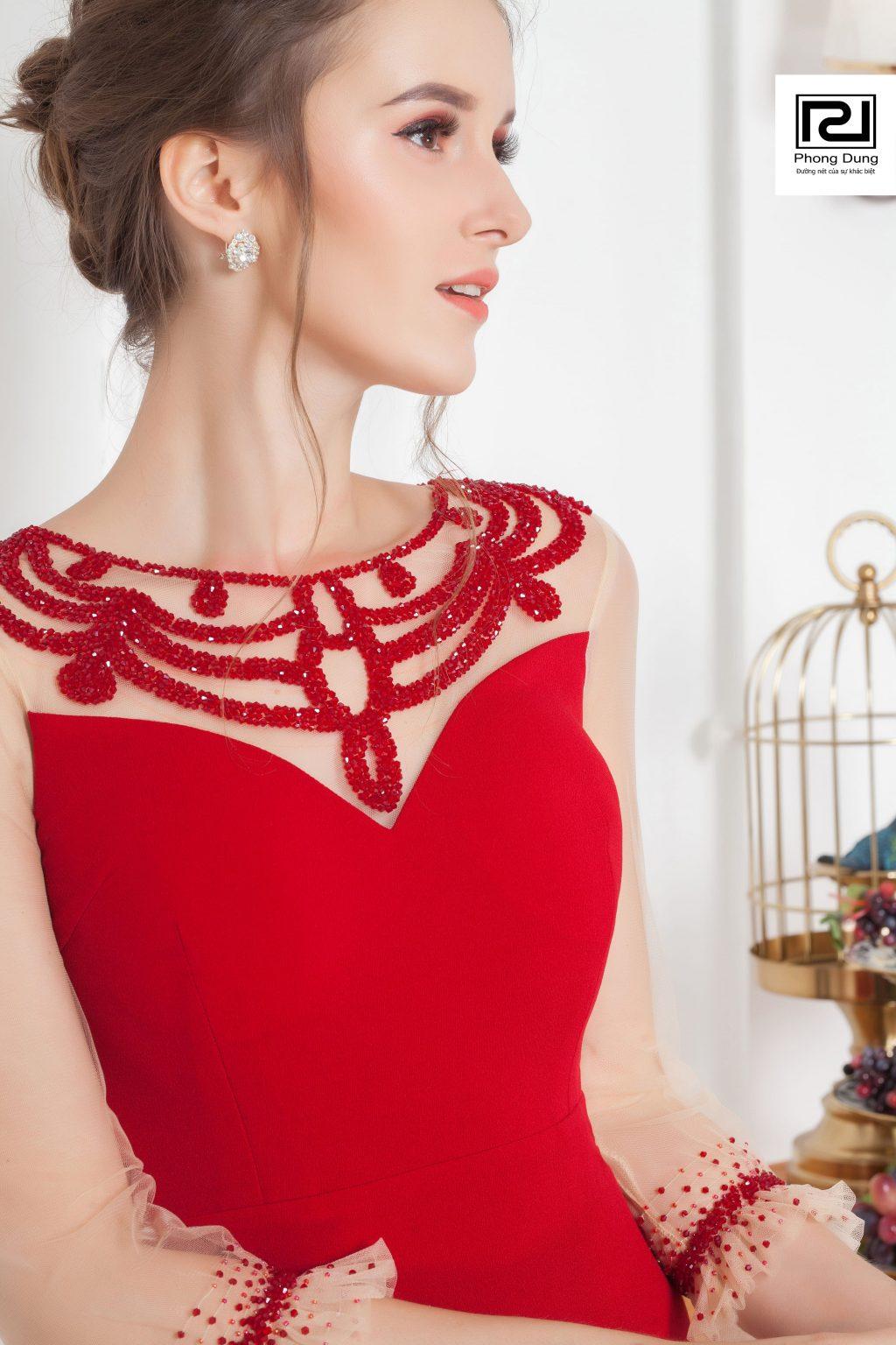 Người mẫu mặc váy ren đỏ mang hoa tai trắng