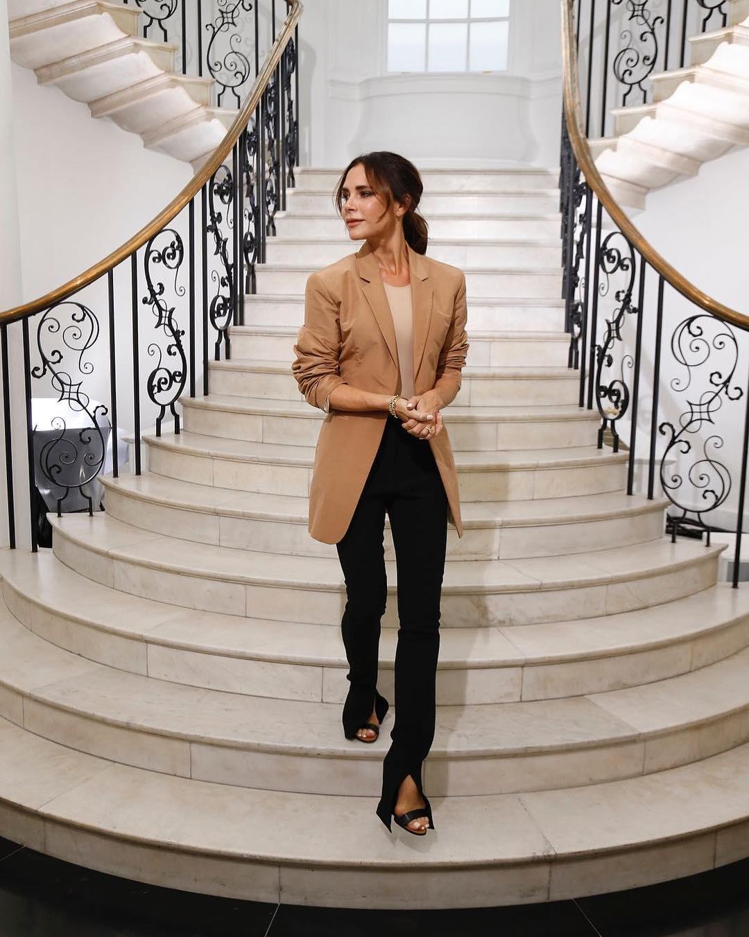 victoria beckham mặc áo khoác màu nâu và quần đen tuần lễ thời trang london